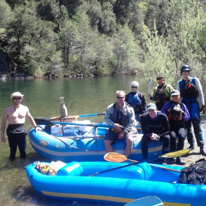 Image of a group sitting on a raft next to the upper sacramento river